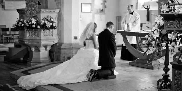 Bride-and-groom-kneeling-at-altar